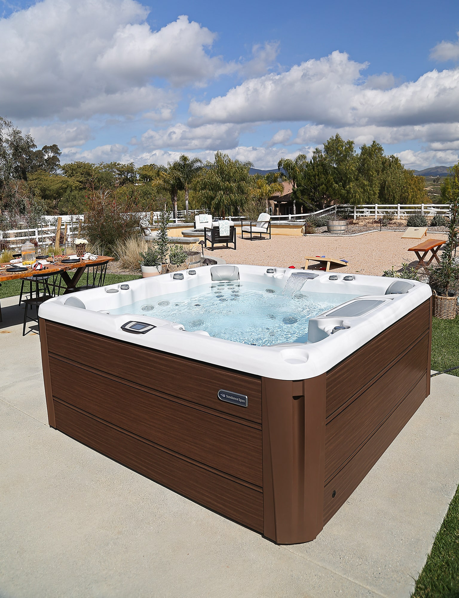 Sundance Spas hot tub installed into a rustic backyard living space